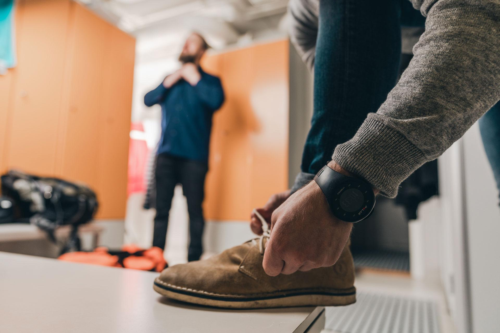 Mies solmii kenkiä pukuhuoneessa ja toinen mies taustalla korjailee kaulustaan.
