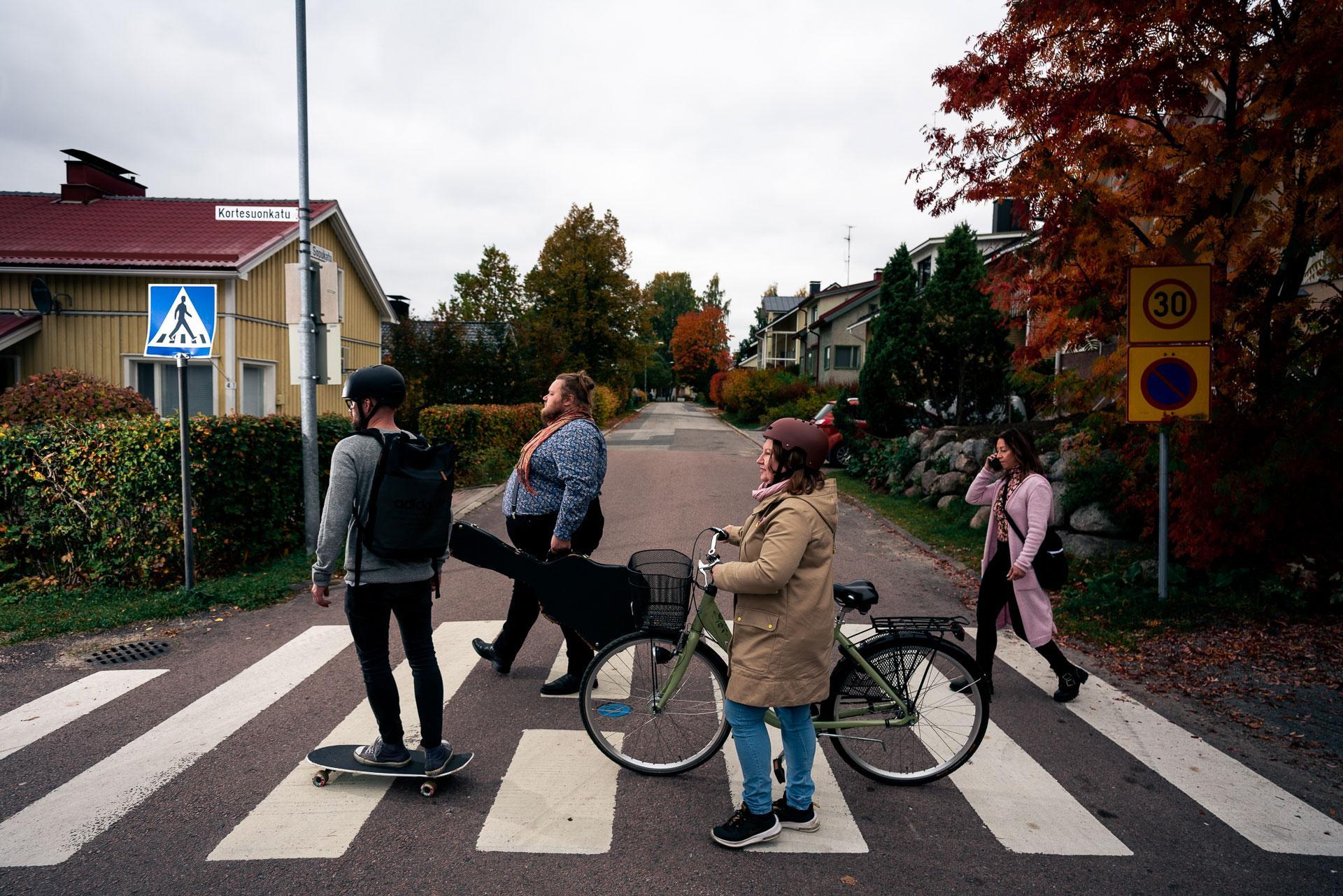 Rullalautailija, pyöräilijä ja kaksi kävelijää ylittävät suojatietä.