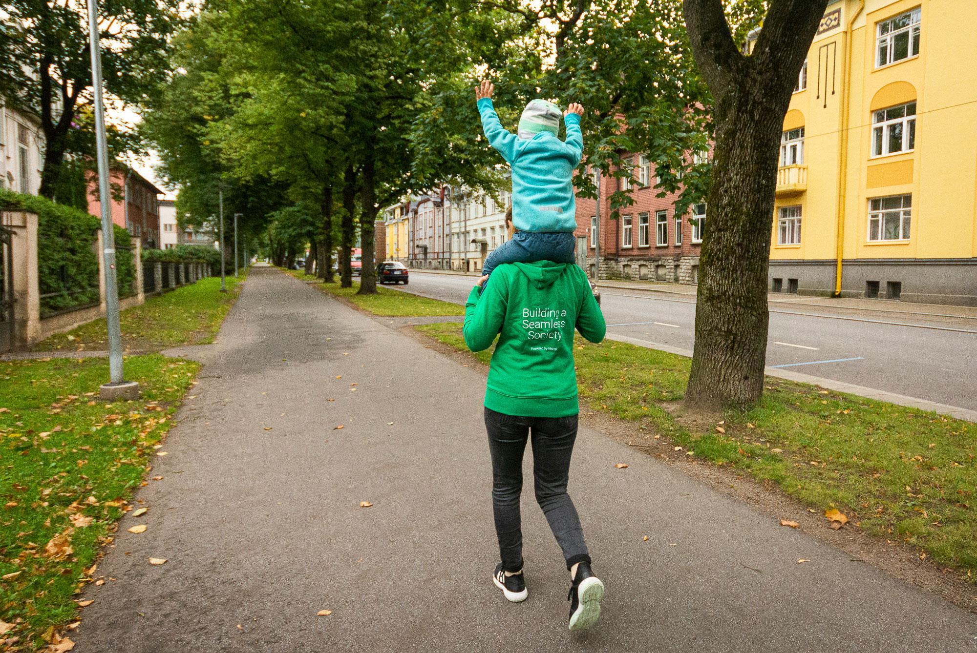 Nainen kantaa lasta reppuselässä kaupungissa kävelytiellä.