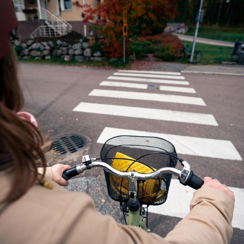 Henkilö ylittää suojatietä polkypyörällä.