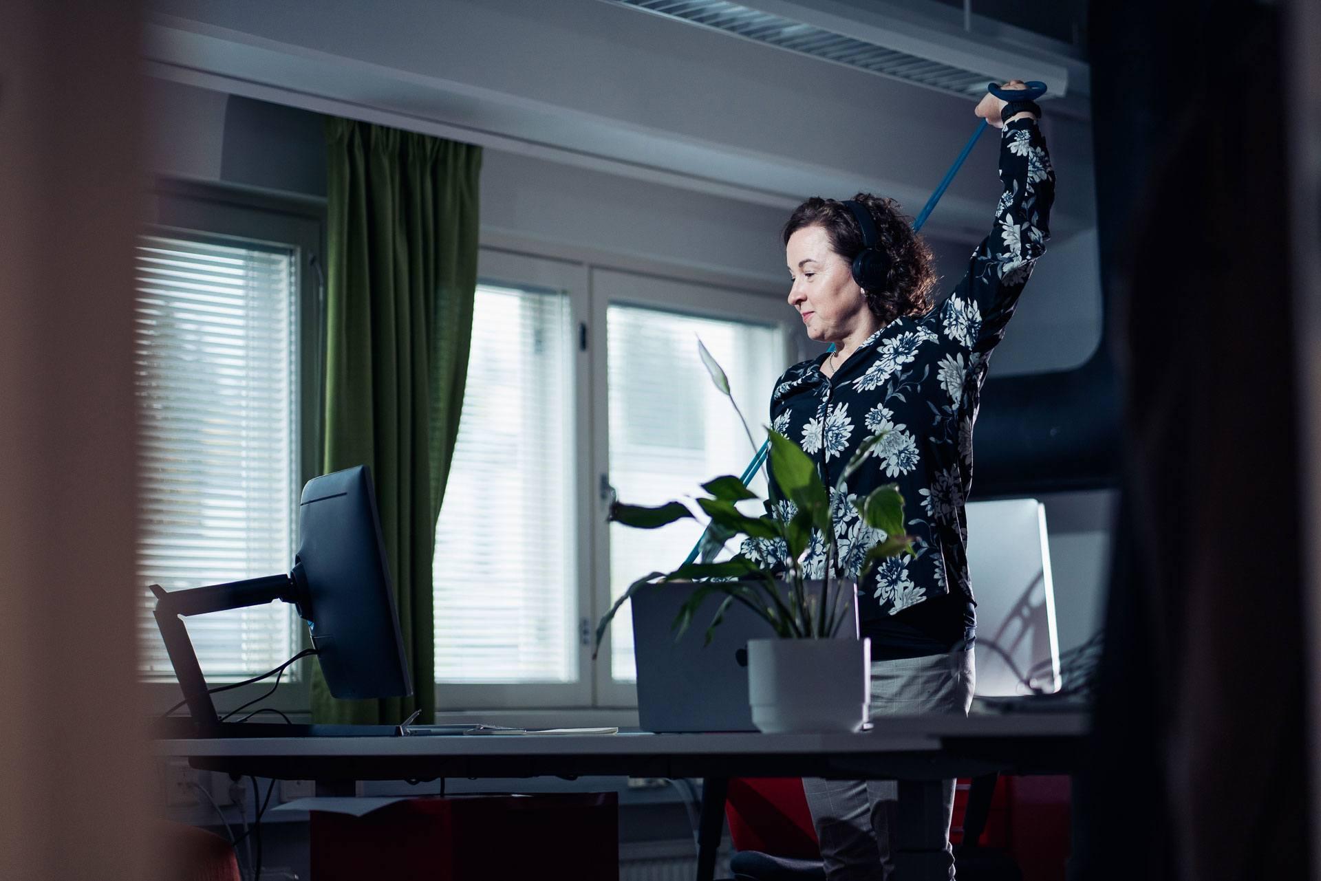 Nainen venyttelee kuminauhan kanssa seisten työpöydän äärellä.