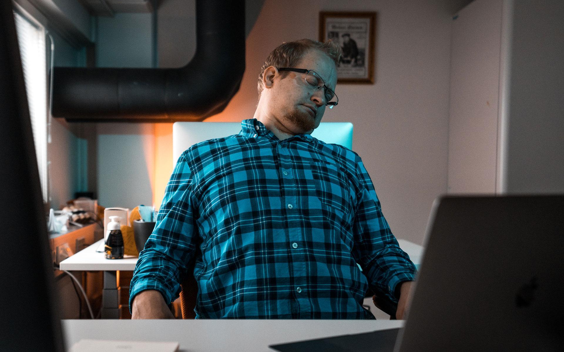 Mies torkkuu työpöydän äärellä.