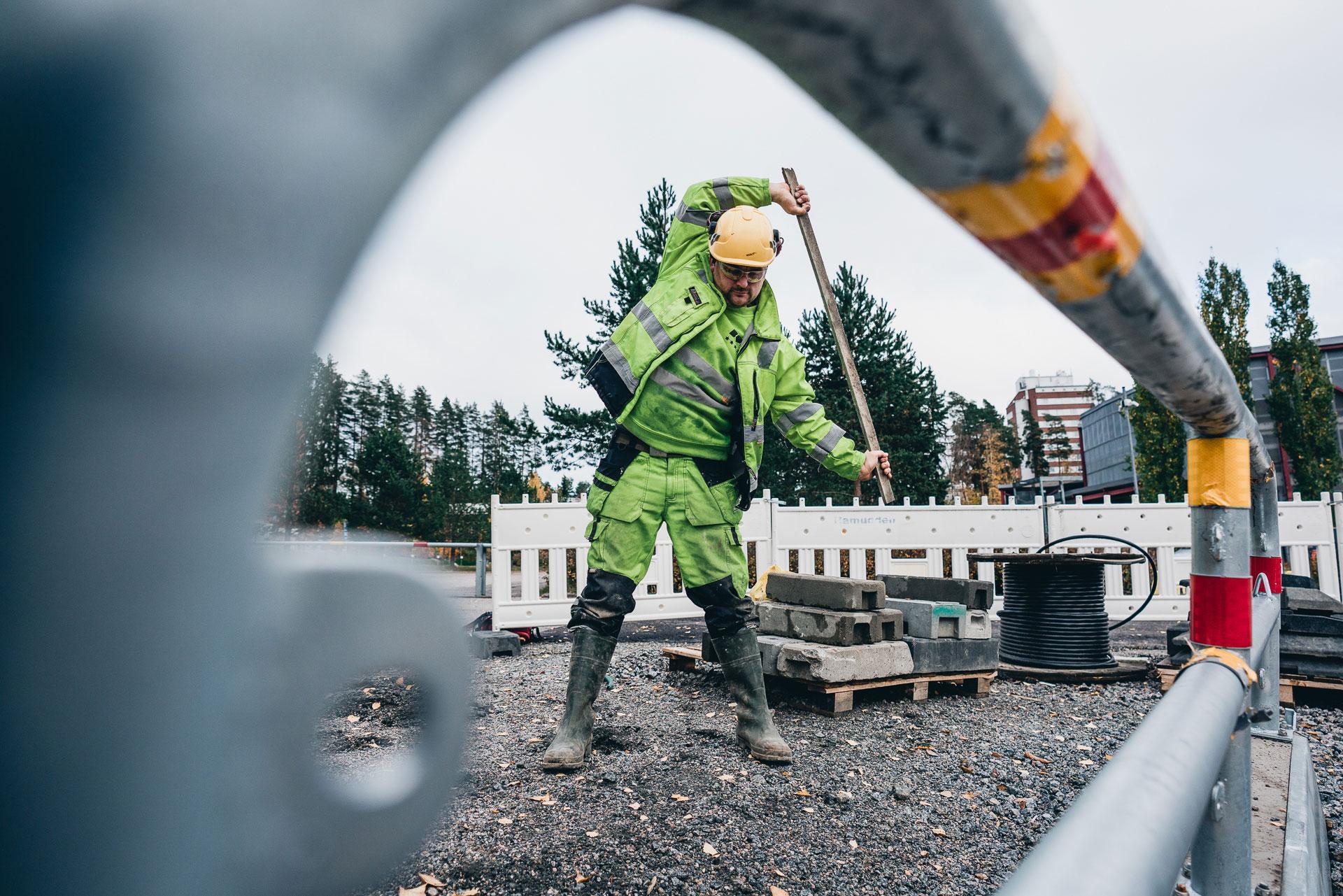 Mies venyttelee rakennustyömaalla kepin kanssa.