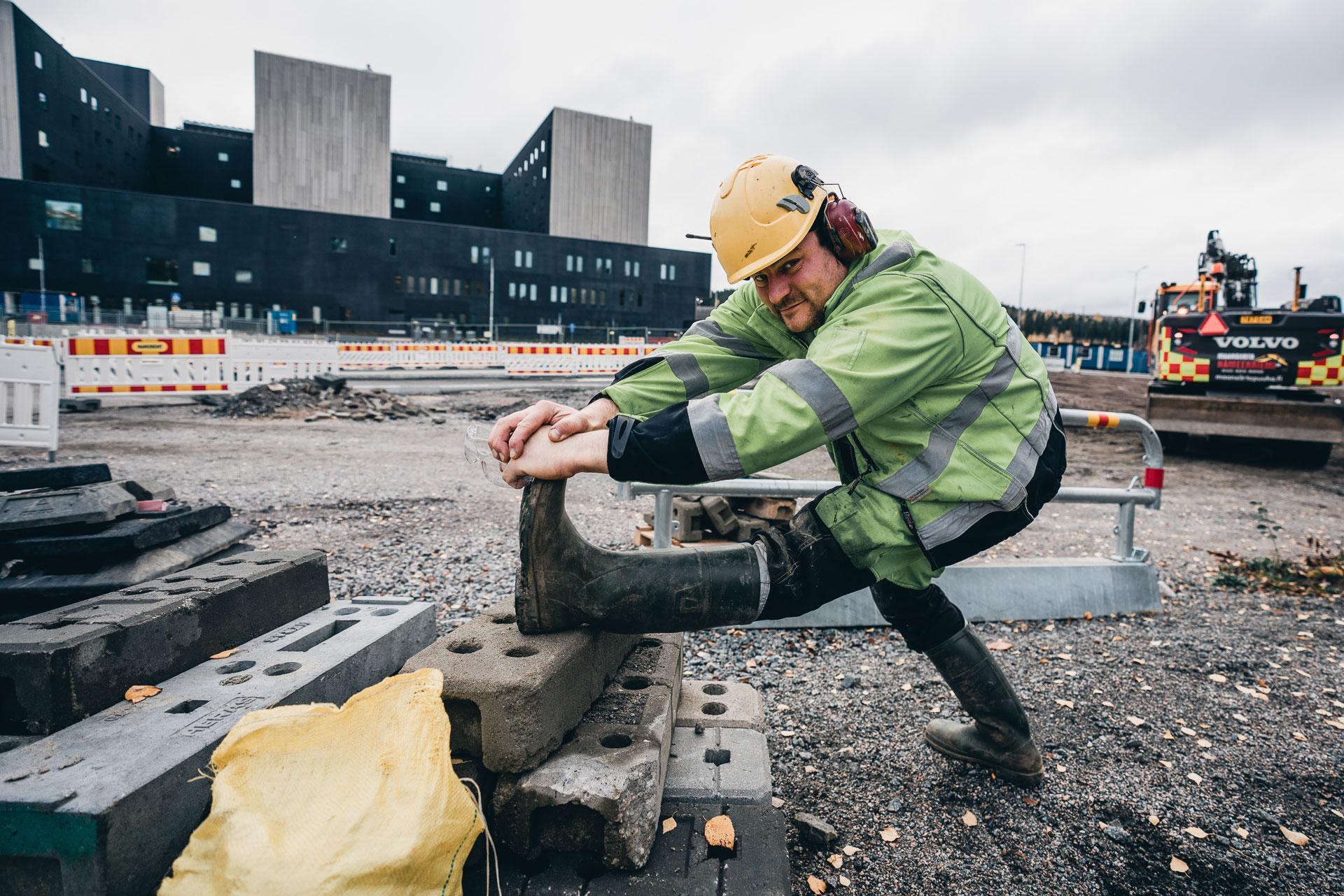 Rakennusmies venyttelee takareittä työmaalla.