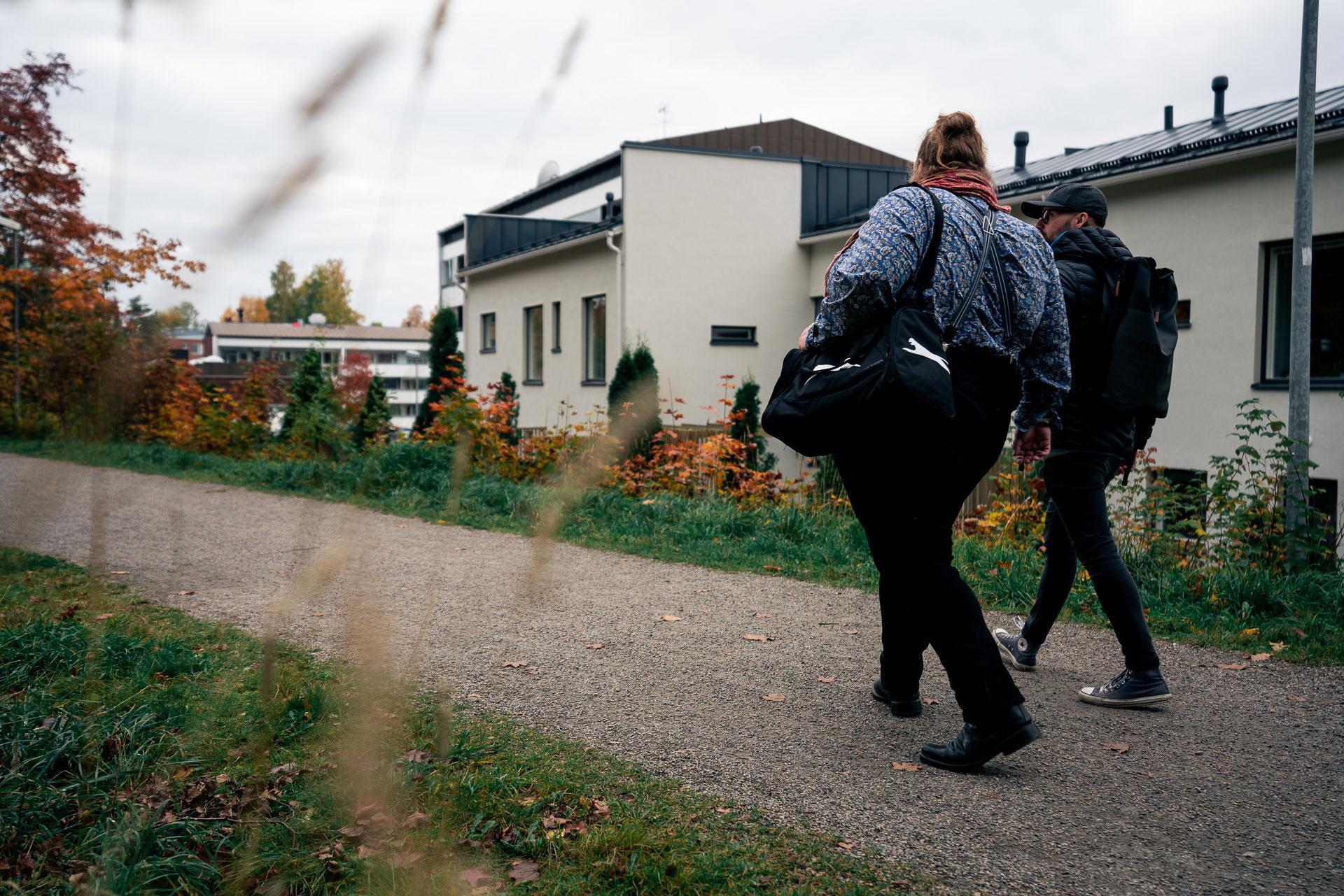Kaksi miestä kävelee kävelytiellä asutusalueella.