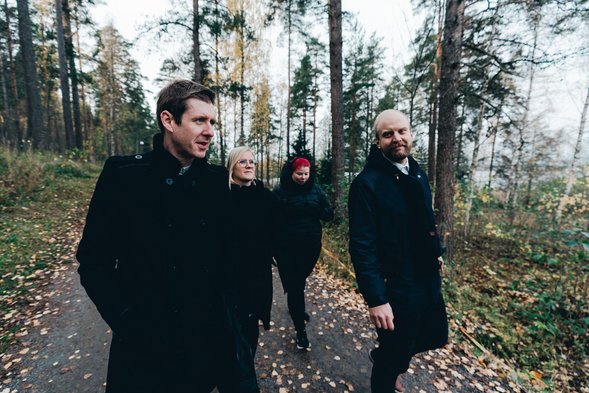 Kaksi miestä ja kaksi naista kävelee metsätiellä.
