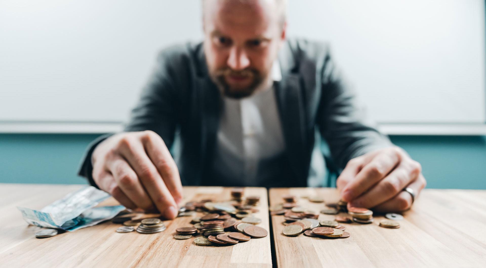 Mies laskee edessään pöydällä olevia rahoja.