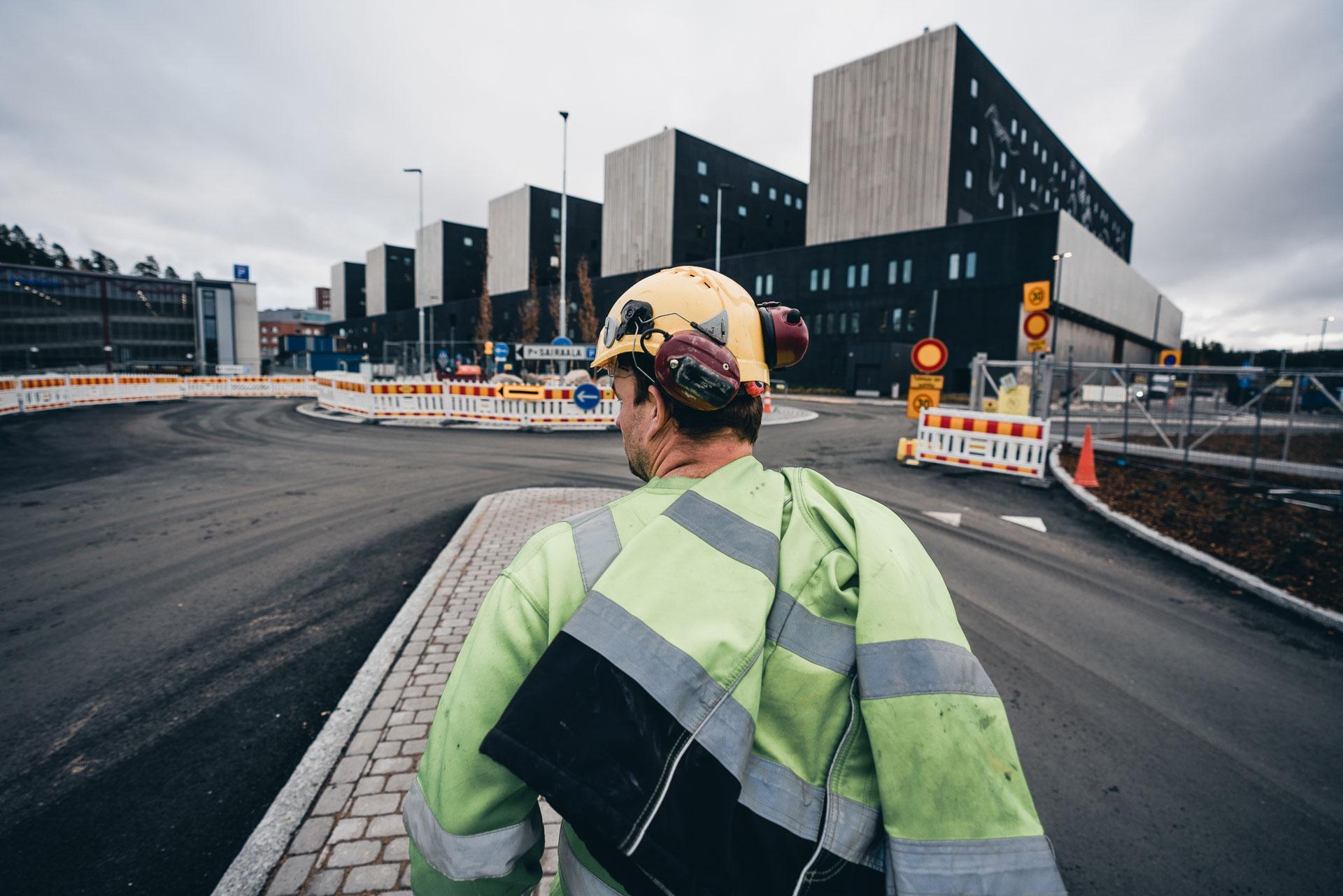 Rakennusmies kävelee rakennustyömaalla.