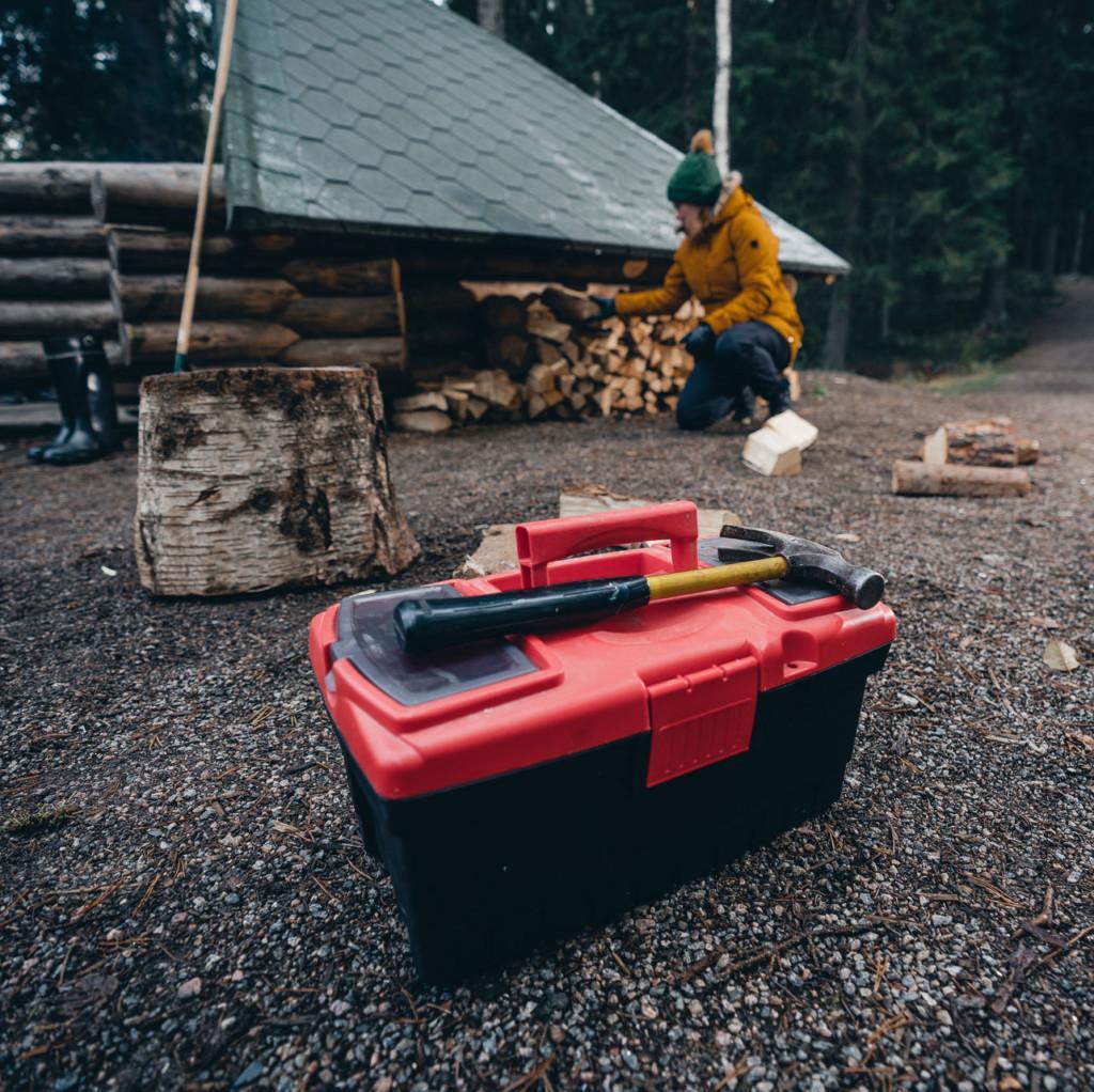 Etualalla työkalupakki, jonka päällä vasara, taka-alalla nainen puuliiterin edustalla.