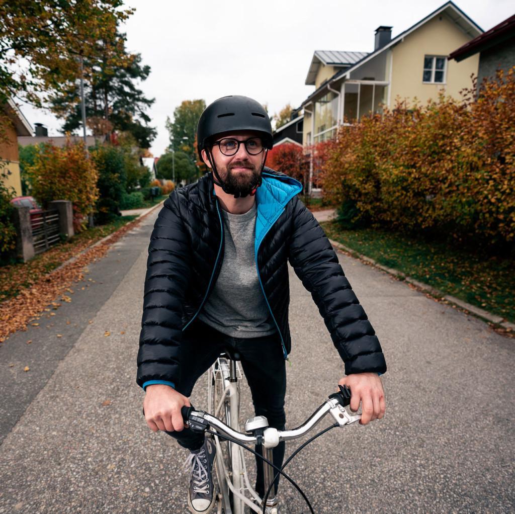 Mies pyöräilee asutusalueella.