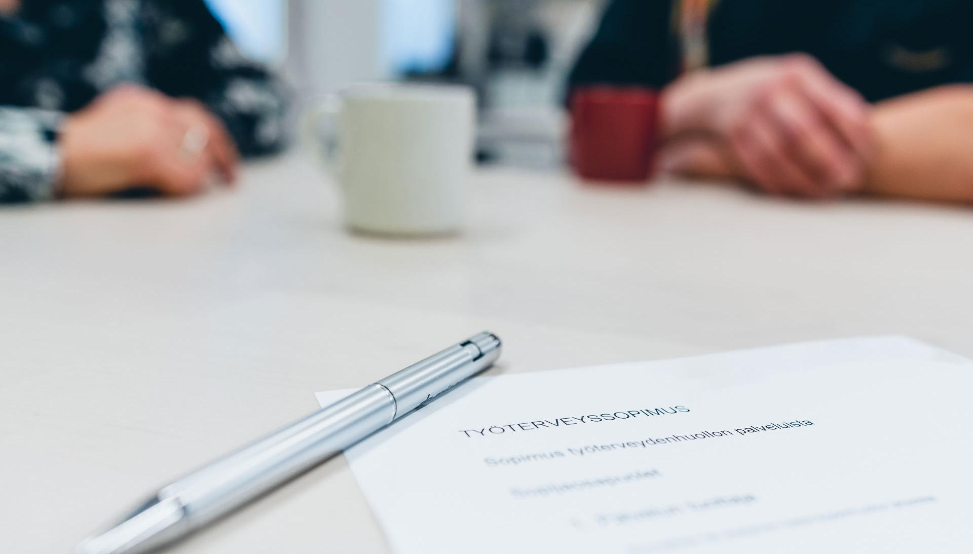 Pöydällä on sopimuspaperi ja kynä sekä taustalla kaksi ihmistä edessään kahvikupit.