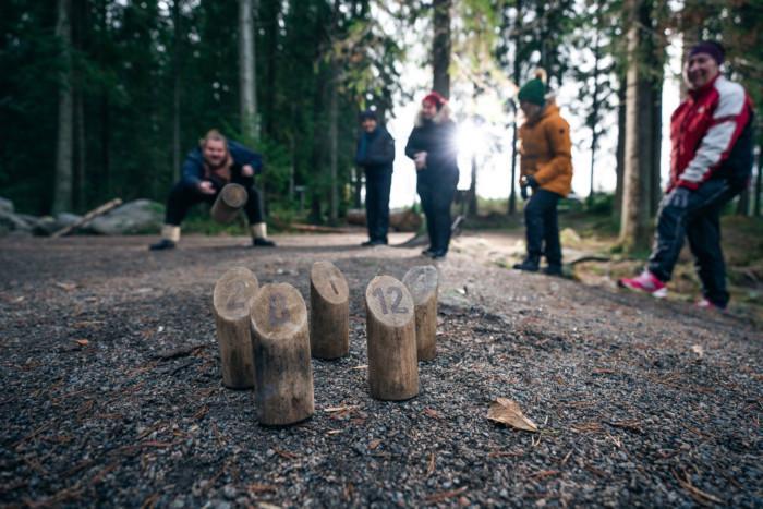 Mies heittää Mölkkyä ja neljä muuta ihmistä katsoo vieressä. Etualalla on viisi Mölkky-palikkaa.