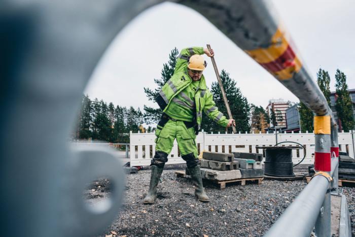 Rakennusmies venyttelee kepin kanssa rakennustyömaalla.