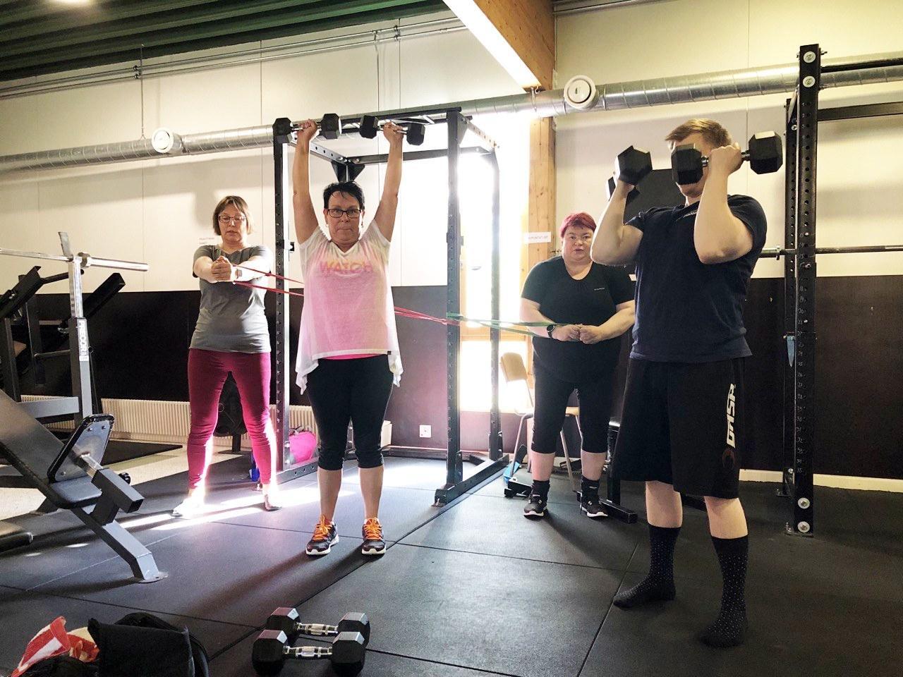 Kuvassa on kolme naista ja yksi mies, jotka harjoittelevat kuntosalilla.